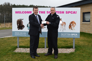 Haydn Davies hands over cheque to Graeme Innes at the SSPCA re-homing centre in Drumoak.