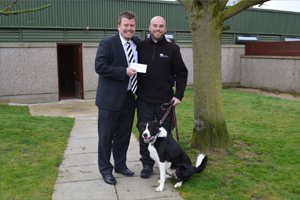Managing Director, Haydn Davies, hands over a cheque to Neil and Sam the collie of Mrs Murray's Home for Stray Dogs and Cats.